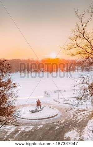 Gomel, Belarus. Sun Rising Over City Park At Winter Morning In Gomel, Belarus.  Scenic View Of River Embankment With Statue Of Ancient Man With His Lynx At Sunrise Or Sunset. Lynx - A Symbol Of City.