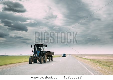 Tractor In Motion On Country Road. Motion Cars On Freeway In Europe.  Asphalt Freeway, Motorway, Highway Against Background Of Eastern European Landscape. Agricultural Concept
