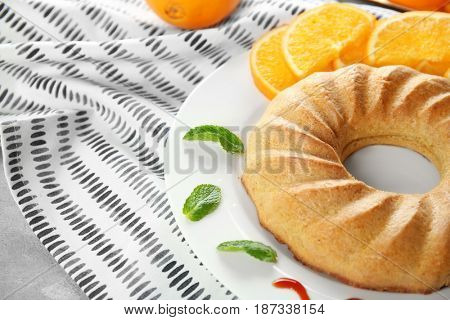 Plate with appetizing citrus cake and orange slices, close up