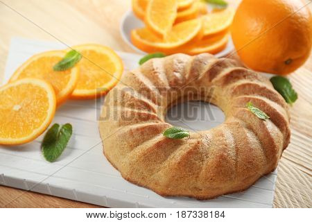 Appetizing citrus cake on wooden board, close up