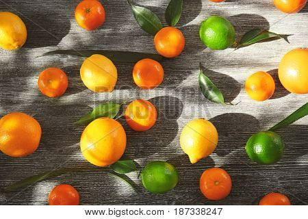 Appetizing fresh citrus fruits on wooden background