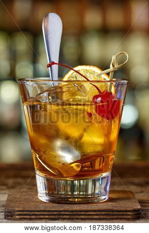Cocktail on the basis of bourbon. American cocktail is old-fashioned. Cocktail stands on a wooden bar in a nightclub
