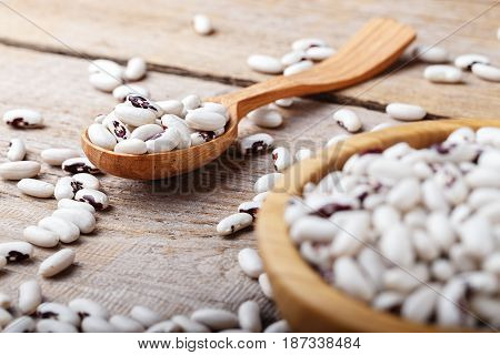 healthy nutritious food uncooked kidney beans scattered on the wooden table in the foreground beans in wooden spoon and in wooden dish