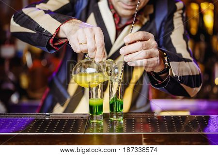 Preparation of a green Mexican cocktail for a drink on the bar barman's hands close up. Horizontal photo