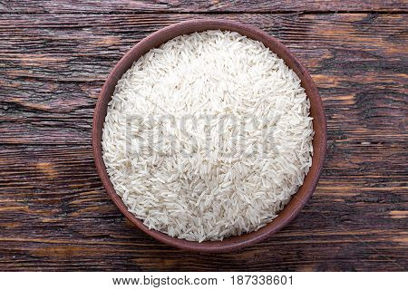 traditional food uncooked rice in a bowl on a wooden background
