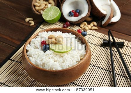 Coconut rice with berries, cashew nuts and lime slice on bamboo mat