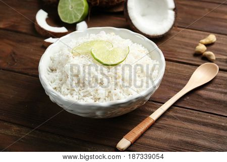 Tasty coconut rice with lime slices on wooden table