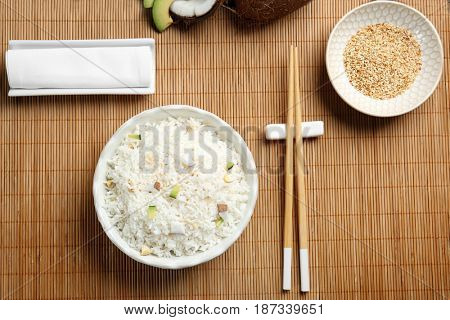 Bowl with coconut rice on bamboo mat