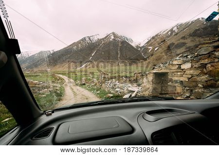 View From Car Window On Old Empty Abandoned Village With Dilapidated Ruined Houses In Ketrisi Village In Truso Gorge, Kazbegi District, Mtskheta-Mtianeti Region, Georgia. Spring Or Summer Season