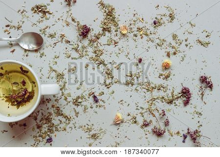 Tea Background. Dry Herbal Tea And Cup Of Hot Tea With Spoon On The Gray Background. Copy Space