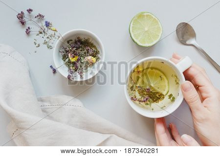 Tea Time. Hands Holding Cup Of Hot Tea. Dry Herbal Tea, Lime And Spoon On The Gray Background, Top V