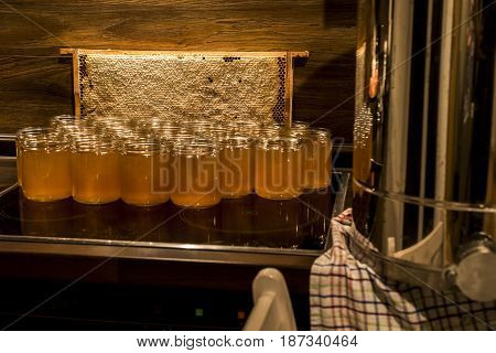 Golden yellow honey in glass jar on wooden board. Closeup. Copy space. comp frame filled