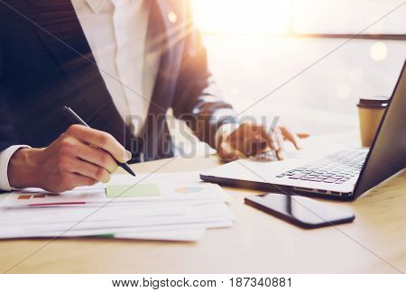 Businessman working at sunny office on laptop.Man pointing notebook keyboard and holding pen hand.Blurred background.Papaer documents on the table.Sunlight effects