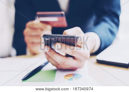 Closeup view of businessman holding credit card in hand and using smartphone, paper documents on the wooden table.Blurred background.Horizontal