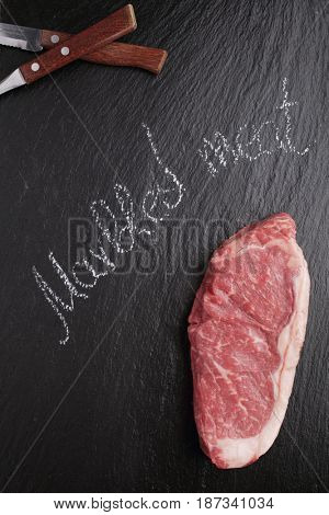 Raw steak of marbled Angus beef meat on a slate cutting board