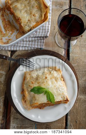 Lasagna Bolognese and red wine on a rustic table