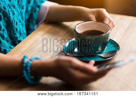 Close up of arms of young woman using mobile phone while drinking cup of coffee. She is sitting at table