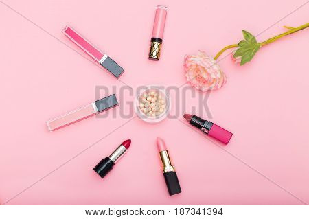 Lip gloss lipstick and powder and a flower on a pink background