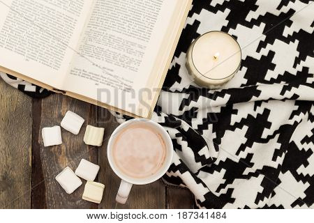 hygge concept. candle blanket hot chocolate book.