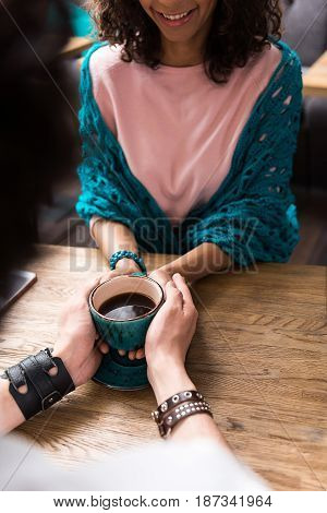 Happy loving couple is drinking coffee together. They are holding mug while sitting at table. Mulatto girl is laughing. Focus on their arms