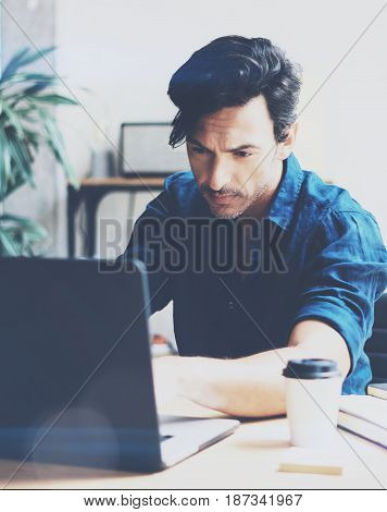 Young handsome man working at sunny office on laptop while sitting at wooden table.Businessman analyze stock reports on notebook computer.Blurred background.Vertical