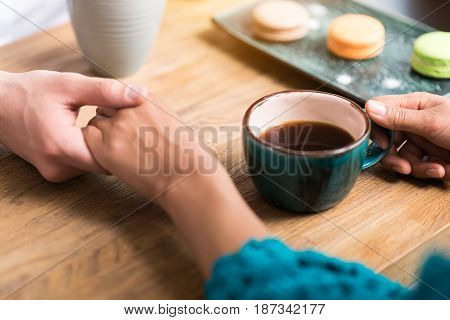 Close up of affectionate young man and woman holding hands on date. Cup of coffee and cookies on table