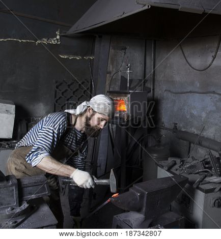 Senior blacksmith working metal with hammer on the anvil in the forge