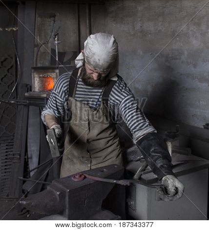 Forge, senior blacksmith's work with hammer, hot metal