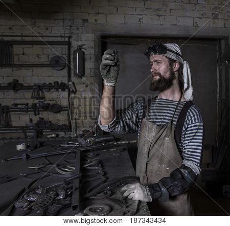 Senior Metalworker preparing for work with iron