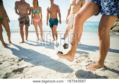 Low section of man balancing soccer ball against friends standing at beach