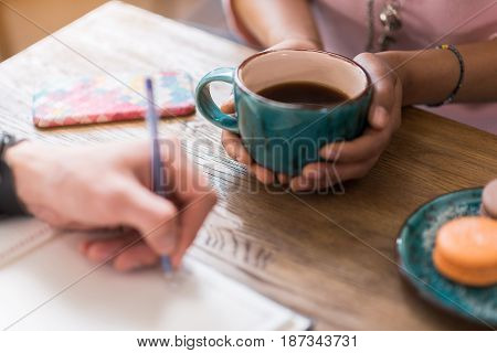 Close up of female arms holding cup of coffee. Woman is sitting at desk near her friend writing in notebook