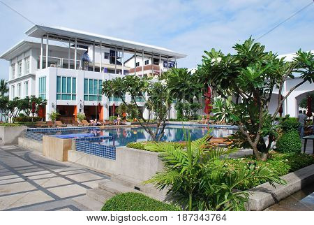 PATTAYA THAILAND - OCTOBER 09 2015: Early morning holidaymakers by the swimming pool in D Varee Jomtien Beach Hotel. It is luxury hotel recreation area.