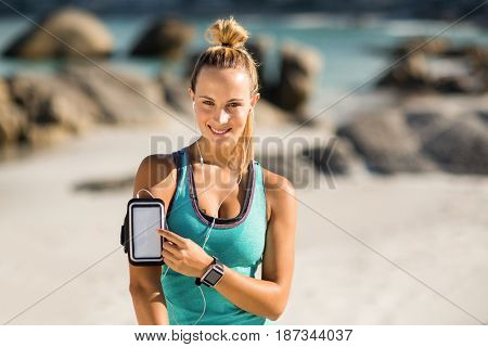 Portrait of young woman touching smartphone on armband at beach