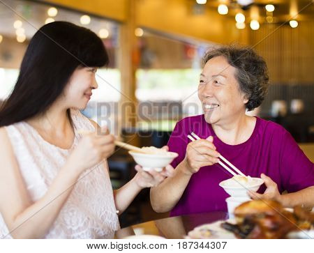 Happy daughter and senior mother enjoy eating in restaurant