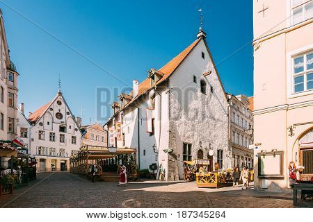 Tallinn, Estonia. Young Woman Dressed In Traditional Folk Costume Dress Walking In Old Town Near Town Hall Square In Sunny Summer Day With Blue Sky