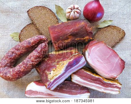 dried meat ham sausage smoked meat pies prepared according to traditional recipes together with bread and vegetables.