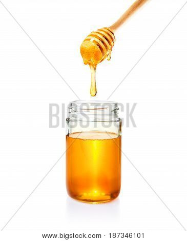 honey in glass jar and dripping from wooden dipper on isolated white bacground