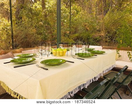 Green dishes on table ready for food to be served outside the garden.