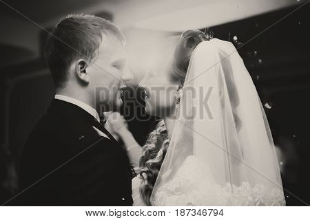 A Black And White Picture Of Newlyweds Hugging Under The Disco Lights