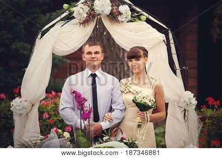 Pretty Wedding Couple Stands In The Front Of Beige Altar