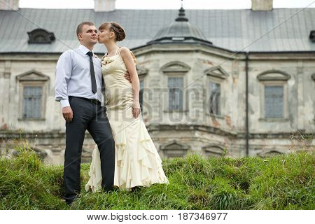 Lady In Dancing Gown Kisses A Man Standing On The Hill In The Front Of A Castle