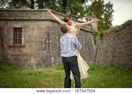 Man Whirls A Stunning Lady Standing Between Stone Walls