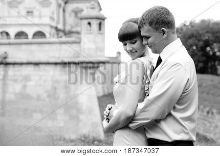Man Hugs Daydreaming Lady From Behind Posing In The Front Of A Castle Wall