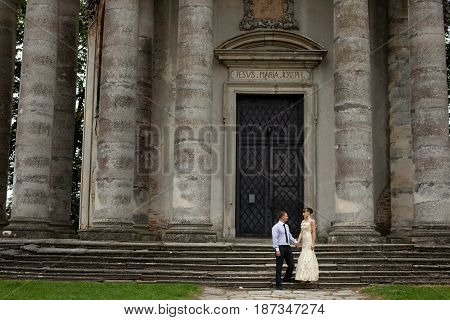 Lady In Dancing Gown Poses With A Man In The Front Of Ruined Cathedral