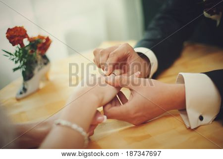 Man adjusts a ring on delicate bride's hand