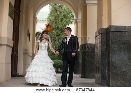 Stunning Newlyweds Walk Under The Archs Outside