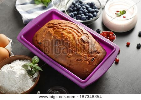 Hot yogurt cake in silicone baking dish with ingredients on table