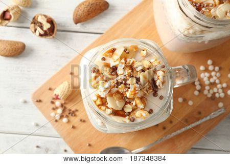 Delicious parfait with granola in jar on board