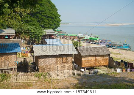 Traditional Burmese houses on the bank of the Irrawaddy river. Mingun, Myanmar