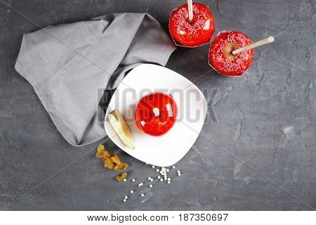 White saucer with candy apple on grey table